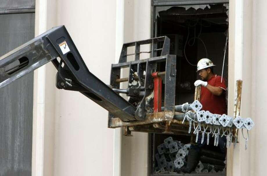 A worker unloads equipment needed to brace the building at 9343 North Loop East where three people died and six were hurt in a wind-driven fire Wednesday. The blaze caused parts of the roof and top floor to collapse. Photo: JAMES NIELSEN, CHRONICLE