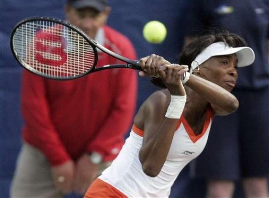 Venus Williams returns a shot during her tennis match with Aravane Rezai. Photo: Phil Coale, AP