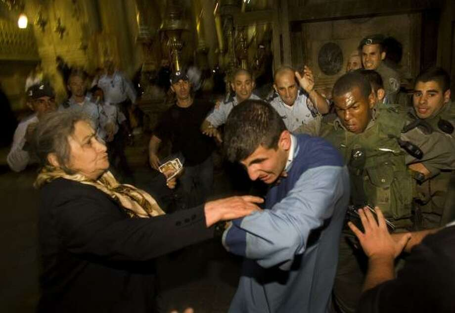 Israeli police scuffle with an Armenian monk next to the site traditionally believed to be the tomb of Jesus Christ at the Church of the Holy Sepulcher in the Old City of Jerusalem, on Sunday, Nov. 9, 2008. A brawl  erupted between rival monks at one of Christianity's holiest sites. Israeli police  detained two monks for questioning. Photo: Bernat Armangue, AP