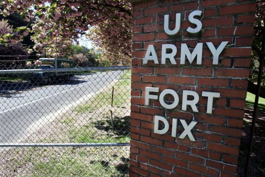 "A truck drives through a Fort Dix Army Base gate on Tuesday, near Wrightstown, N.J. Six men described by federal prosecutors as ""Islamic militants"" have been arrested on charges they plotted to ""kill as many soldiers as possible."" Photo: Mel Evans, AP"