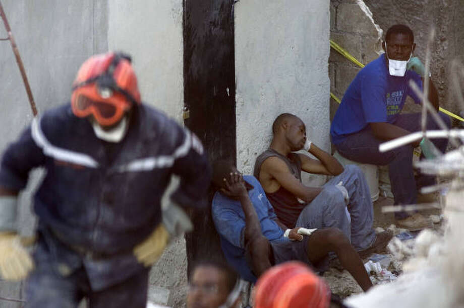 Rescue workers rest at the 'La Promesse' school after it collapsed in Petionville, Haiti, Saturday. Photo: Ramon Espinosa, AP
