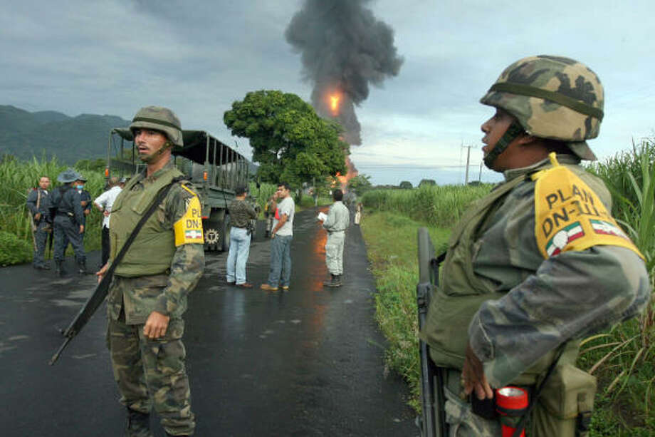 Mexican Army soldiers stand on a road as a pipeline fire rages Monday near the town of Omealca in the state of Veracruz, Mexico. Photo: Luis Monroy, AP