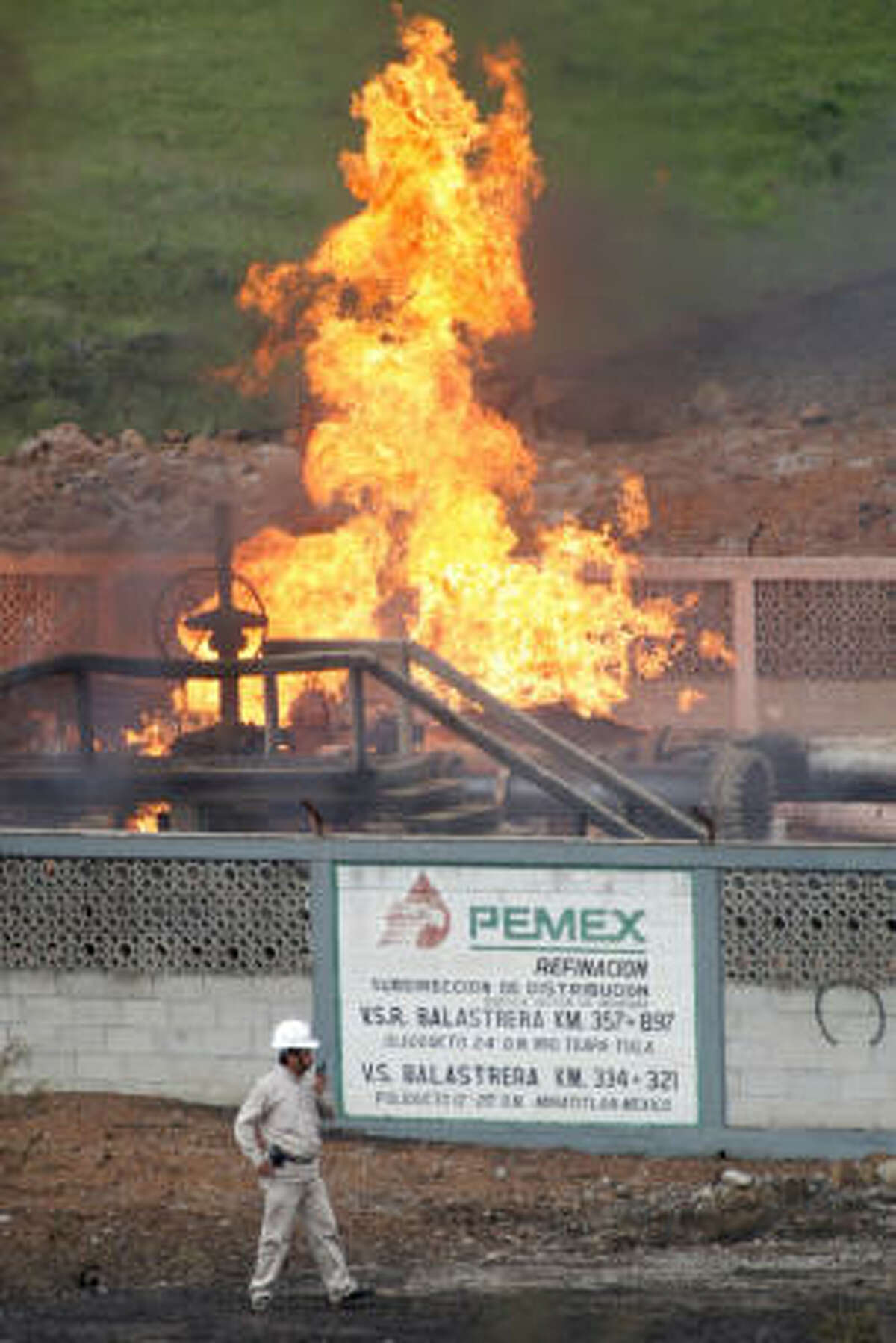 A worker talks on a radio in front of a burning facility of the state oil company Pemex near Maltrata, Mexico.