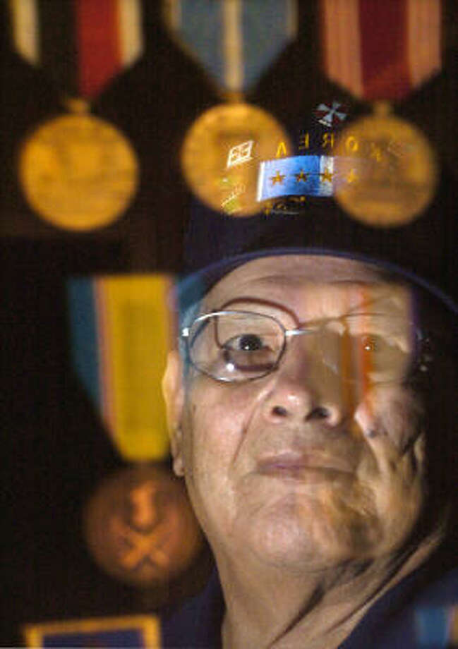 "Henry Martinez, 75, of Houston, poses with combat medals he earned for serving in Korea. While he says ""we are not fighting (the Iraq war) the right way,"" he backs sending more troops, if necessary. Photo: Johnny Hanson, For The Chronicle"