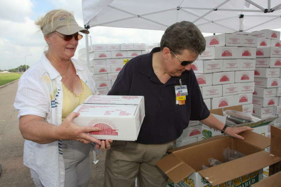 POINT OF DISTRIBUTION:  Volunteers Shirleen Willis of Stafford and Janie Sargent of Houston  select food packages Sept. 22 for storm victims at the Stafford POD at the Southern Ice Cream Corp., 13755 Greenland Drive . Photo: Suzanne Rehak, For The Chronicle