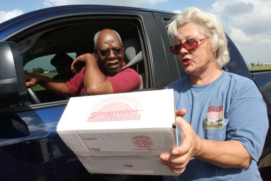 Eugene Harris of Alief listens as Stafford POD volunteer Linda Chumley of Meadows Place reads the contents of a box of foods. Photo: Suzanne Rehak, For The Chronicle