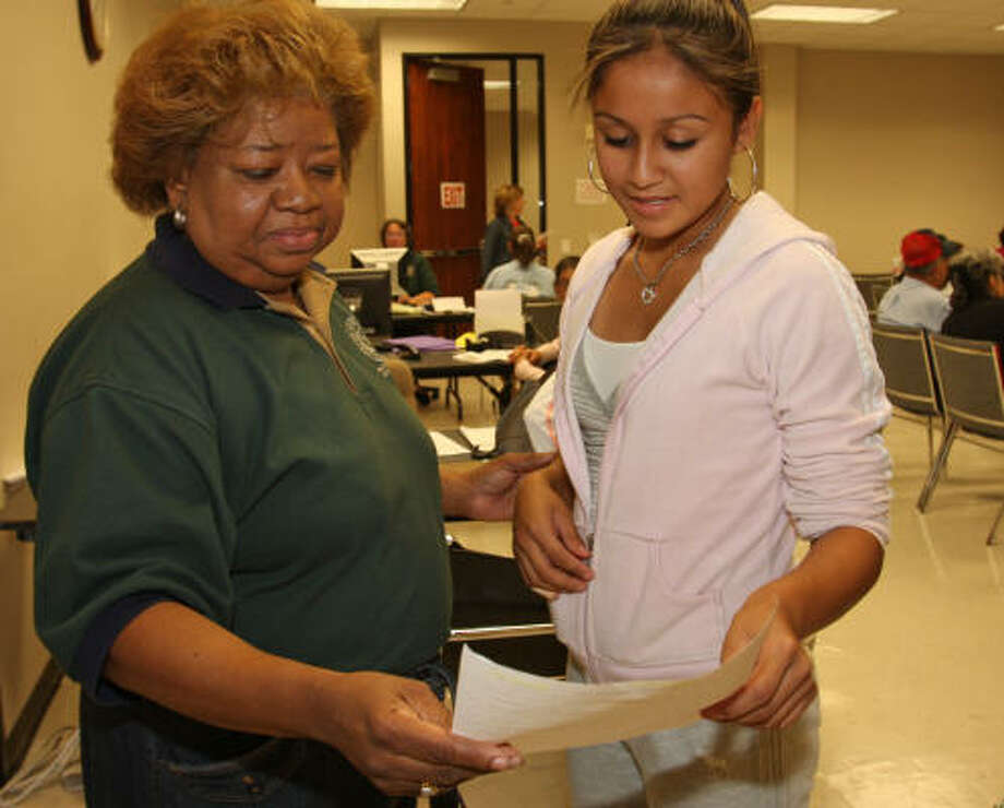 Hopie Solomon, left, director of Human Services reviews an application that volunteer Anyssa Silva, 16, Terry High School 11th-grader, shows her. The application for a food voucher was completed by a victim of Hurricane Ike at the Fort Bend County Rosenberg Annex, 4520 Reading Road. Photo: Suzanne Rehak, For The Chronicle