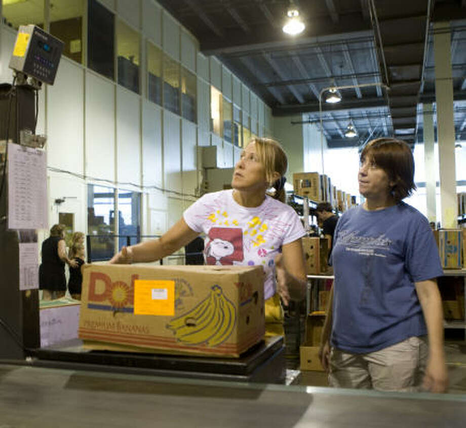 NEIGHBORS HELPING NEIGHBORS:  Julie Gawel, left, of Katy and Beverly Smith of Stafford weigh boxes of sorted food donations on Sept. 17 at the Houston Food Bank prior to shipping the donations to victims of Hurricane Ike. Photo: Jason Brown, Special To The Chronicle