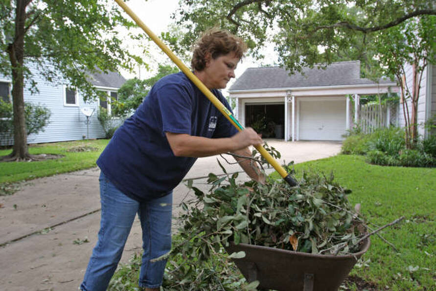 Melissa Allen of the 1200 block of MacArthur Street in Rosenberg, cleans her front yard after Hurric