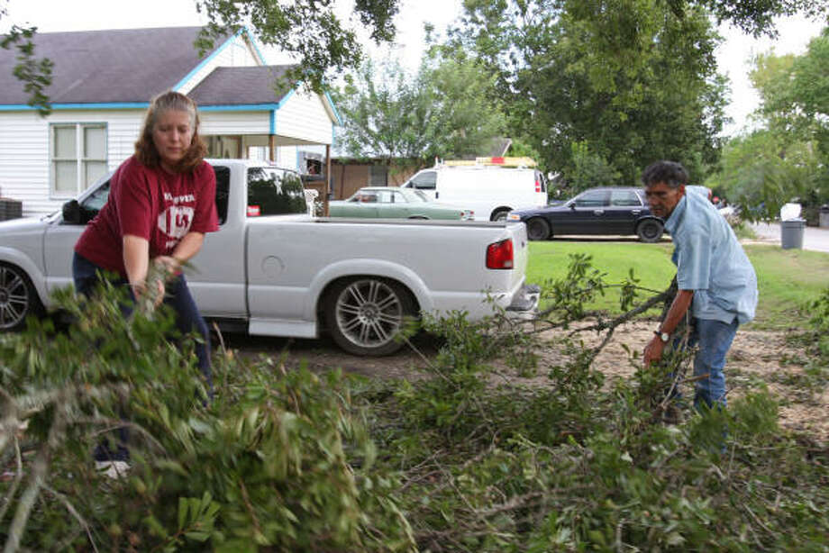 From left, Colleen McCarthy and Manuel Pina in the 1700 block of Fifth Street in Rosenberg, clean up their front yard after Hurricane Ike. Photo: Suzanne Rehak, For The Chronicle