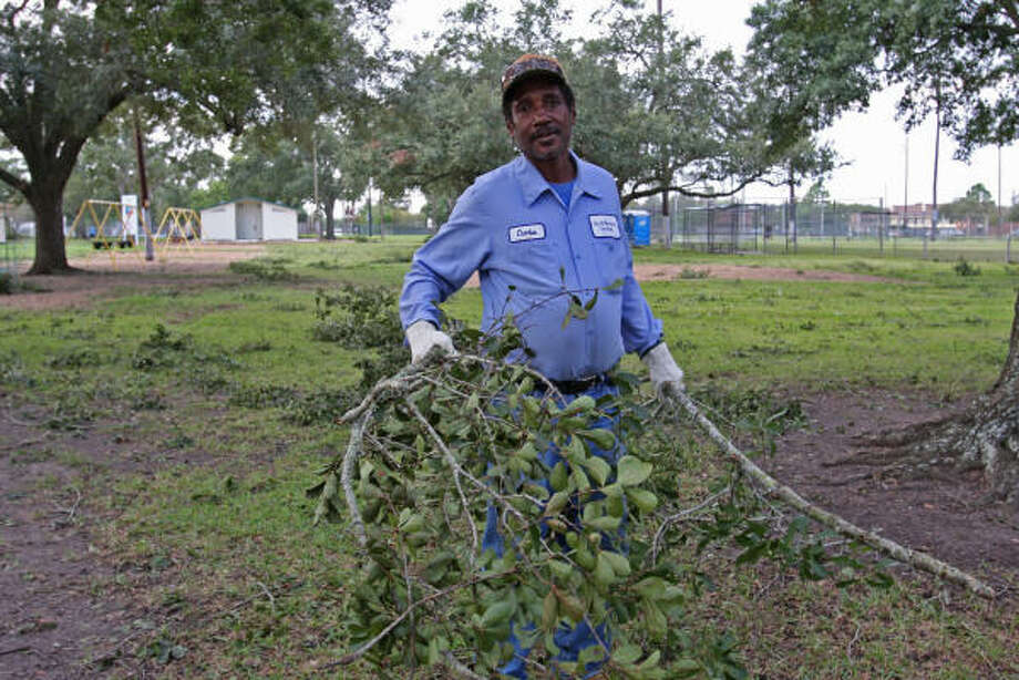 Charles Posey, City of Rosenberg Parks Department employee, picks up broken limbs at Travis Park at Damon and Avenue L in Rosenberg after Hurricane Ike. Photo: Suzanne Rehak, For The Chronicle