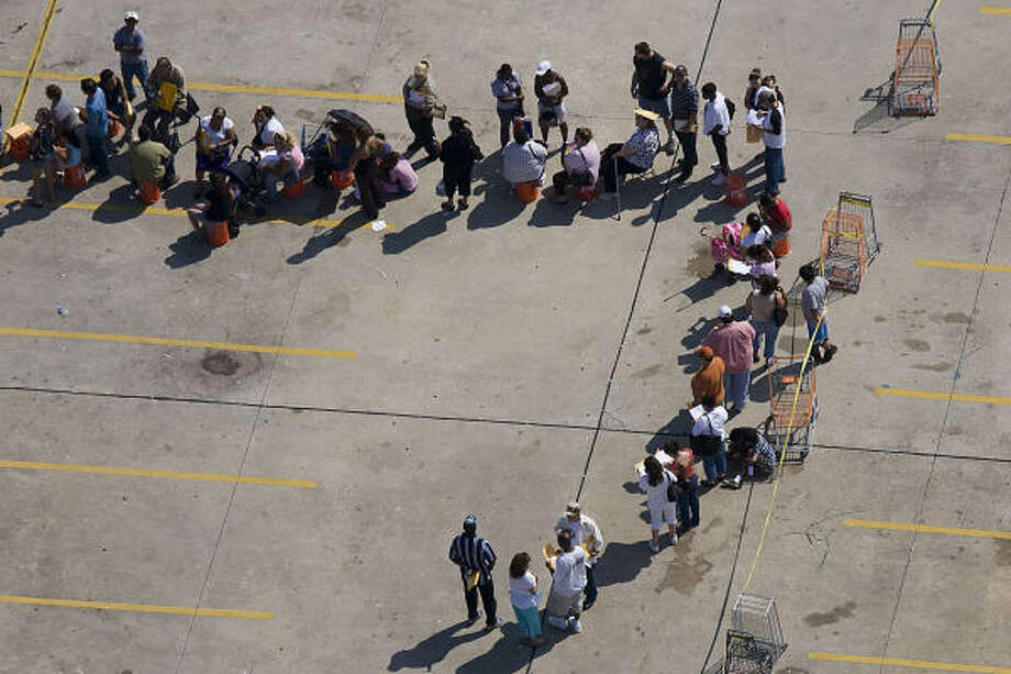 A line of people wait for disaster assistance in a parking lot off of Interstate 45 near Beltway 8 in Houston. Photo: Smiley N. Pool, Chronicle