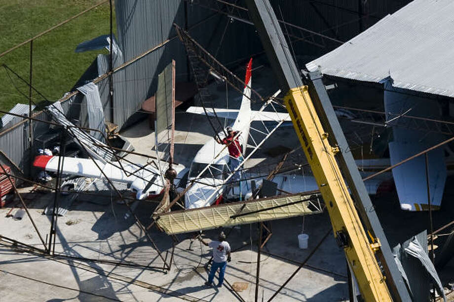 Workers remove debris from a damaged hanger at Weiser Air Park Cypress. Photo: Smiley N. Pool, Chronicle