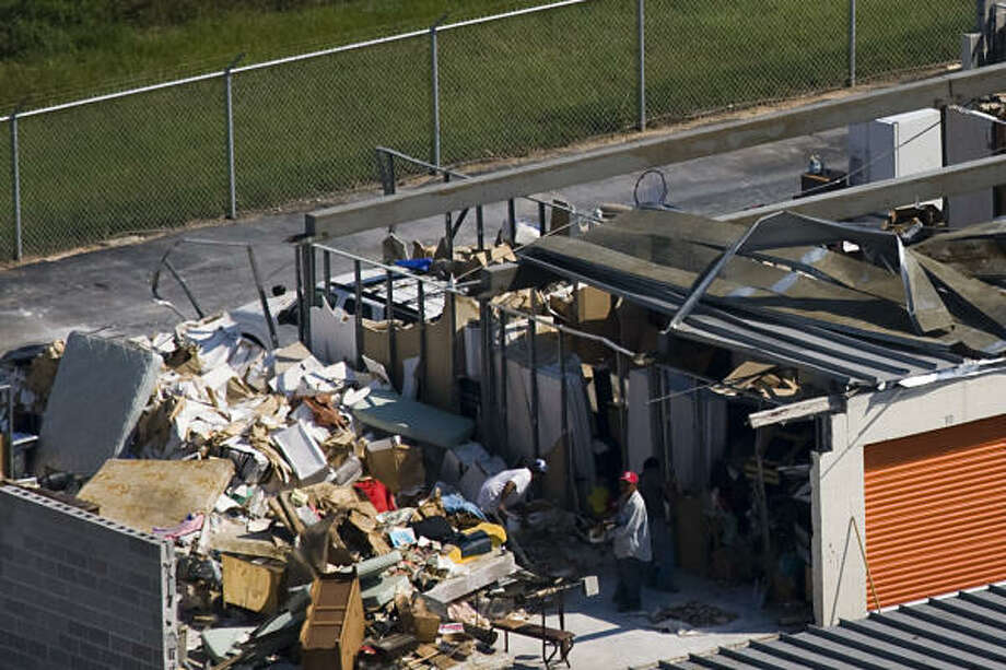 Men pick through the debris of a damaged self storage facility on the Interstate 45 near FM 1960 in Houston. Photo: Smiley N. Pool, Chronicle