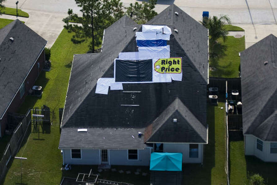 Various materials are seen used to cover a damaged roof in Northwest Houston.
