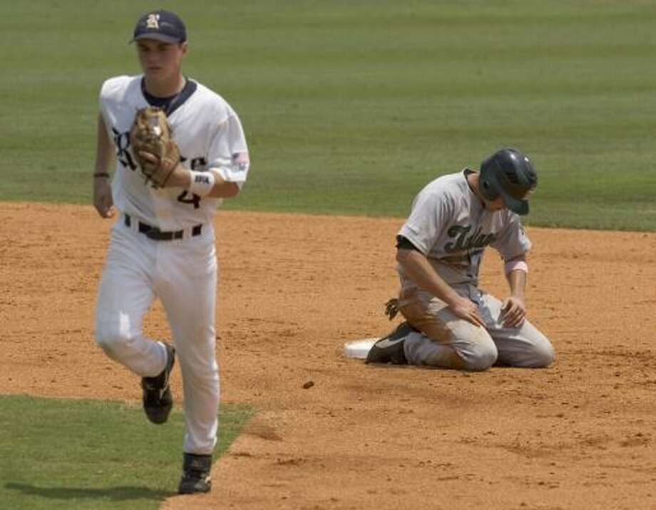 Cat Everett is left holding the bag after Rice's Brian Friday, left, turns a double play to end the third inning. Photo: BRETT COOMER, CHRONICLE
