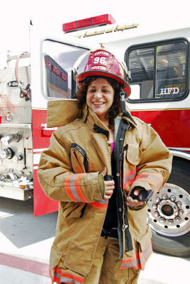 Marketing Coordinator Lauren Rendon took the opportunity to try on a firefighter's outfit. Photo: Tony Bullard, For The Chronicle