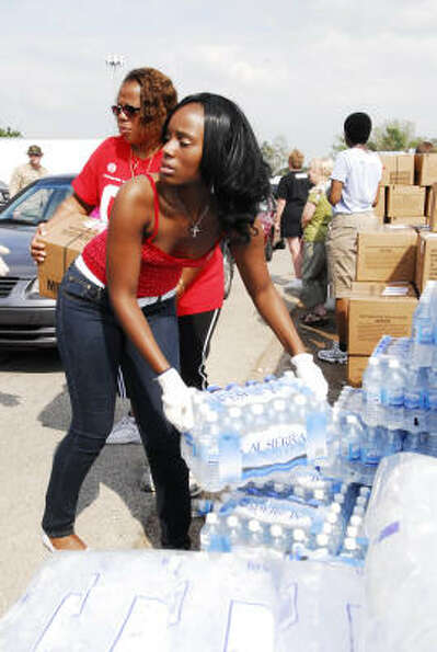 Cy-Springs senior DeShawn McLain, 17, grabs a case of bottled water to load into cars at the Church