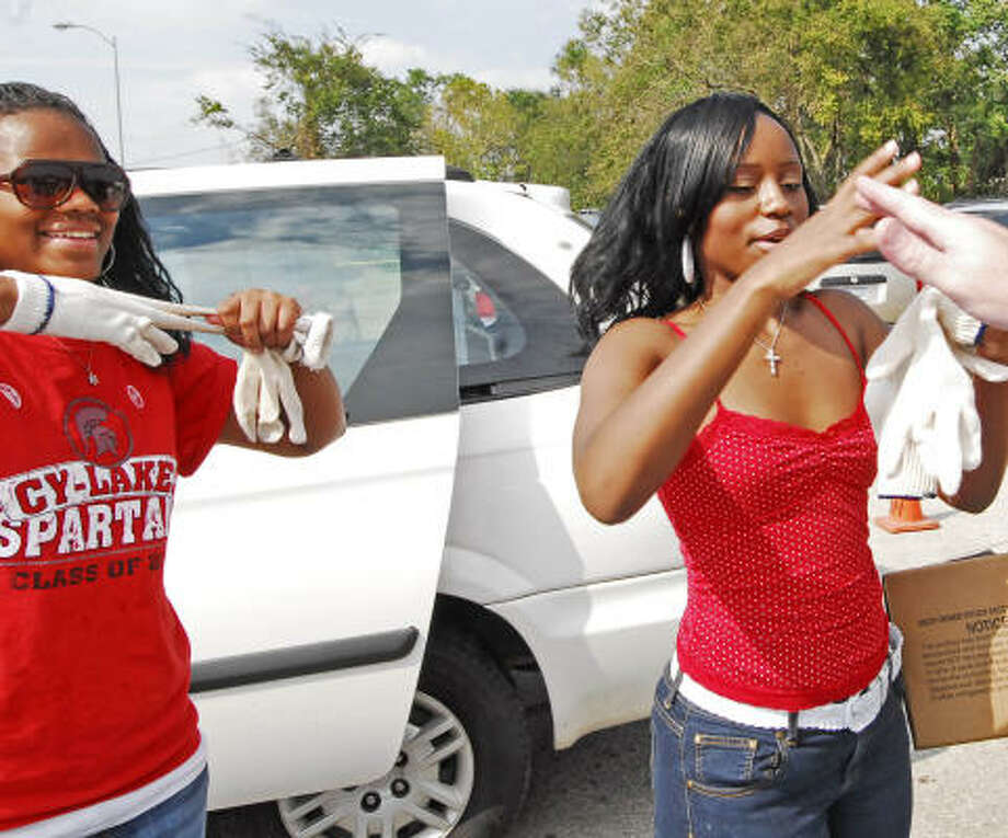 Cy-Lakes freshman Lynnell McLain, 14, left, and her sister, Cy-Springs senior DeShawn McLain, 17, take off their gloves as a shift change of volunteers gives them a few moments to take a breather at the Church Without Walls POD site. Photo: Tony Bullard, For The Chronicle