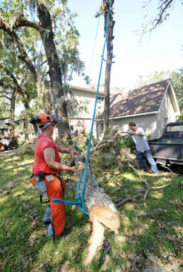 Brett Landsman, left, and Leo Tartick of St. Matthew's Tree Services, based in Buffalo, NY, remove branches at a house on Woodedge Drive. Photo: Thomas Nguyen, For The Chronicle