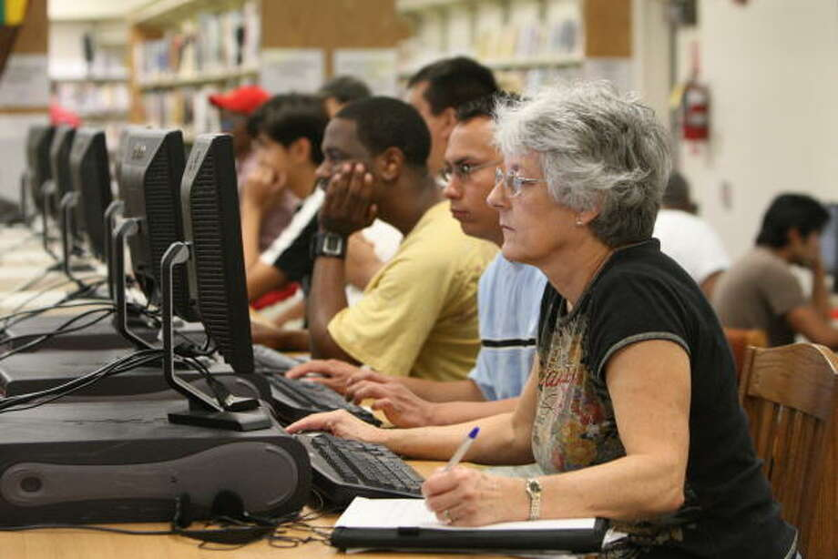 Millridge Forest residents Karen Butts, foreground, William Chispas, and others who still don't have electricity in the area take advantage of Northwest Branch Library's Internet services on Sept. 20. Photo: Thomas Nguyen, For The Chronicle