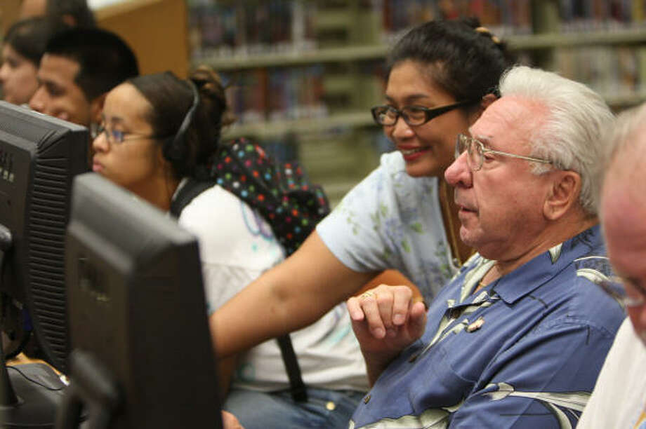 Librarian Connie Villa assists nearby Lakewood Forest resident Robert Nagy, who still doesn't have power nor phone services, at Northwest Branch Library on Sept. 20. Photo: Thomas Nguyen, For The Chronicle