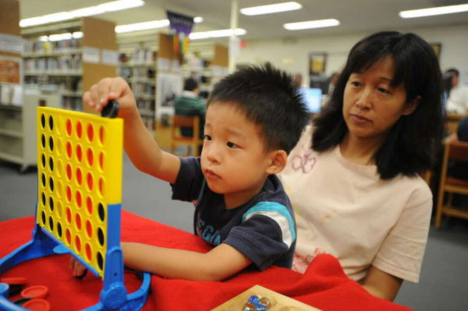 Nearby resident Young Lee brings her son Andrew, 3, to Northwest Branch Library for some fun activities because her house still lacks electricity. Photo: Thomas Nguyen, For The Chronicle