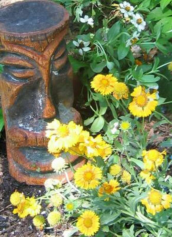 Yellow gaillardia blooms in front of a Tiki man carved by Crystal Beach craftsman Kevin Kavanaugh. Photo: BRENDA BEUST SMITH