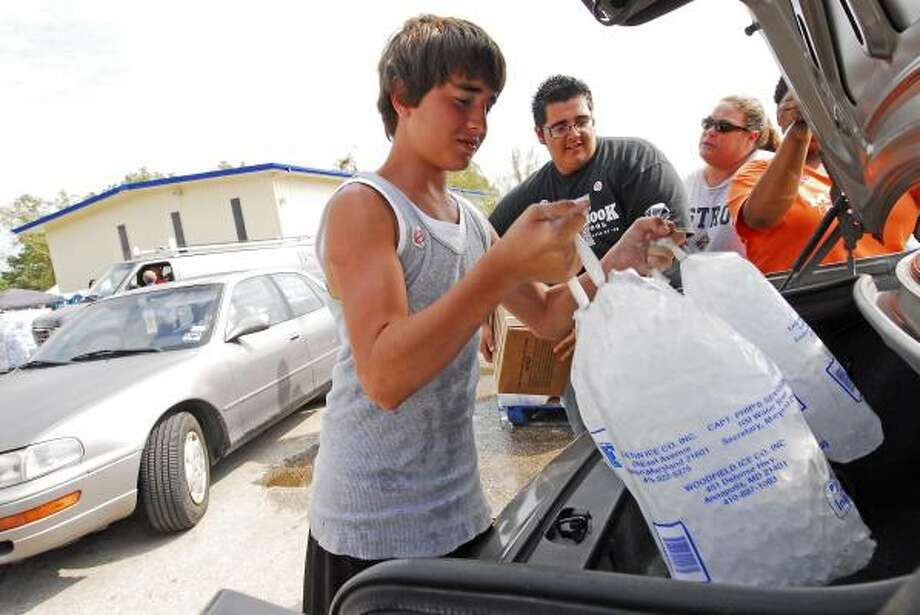 Troy Herrera, 14, loads bags of ice into a cars at the Church Without Walls POD site. In the background are Osbaldo Castillo and Renee McLean. Photo: Tony Bullard, For The Chronicle