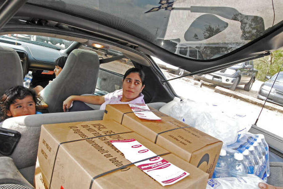 Lupe Gonzales, right, and daughter Gabriel watch as volunteers lod cases of meals, ready-to-eat (MRE's) and water and ice into the back of her family's car at the Church Without Walls POD site. Photo: Tony Bullard, For The Chronicle