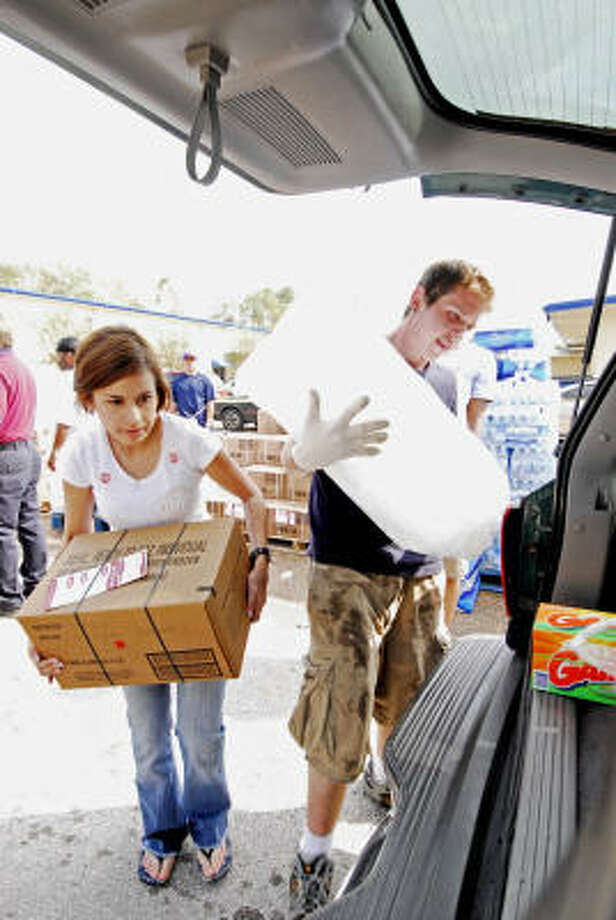 Dafne Basave loads cases of meals ready-to-eat (MRE's) and Casey Josleyn loads bags of ice into cars as people drive through the the Church Without Walls POD site. Photo: Tony Bullard, For The Chronicle