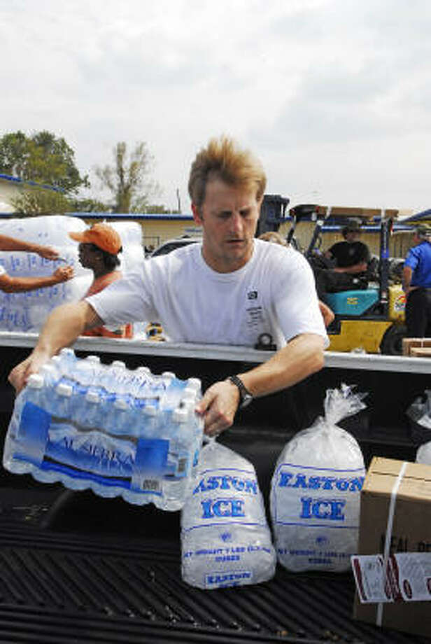 Drew Wasson loads cases of bottled water into cars as people drive through the Church Without Walls POD site. Photo: Tony Bullard, For The Chronicle