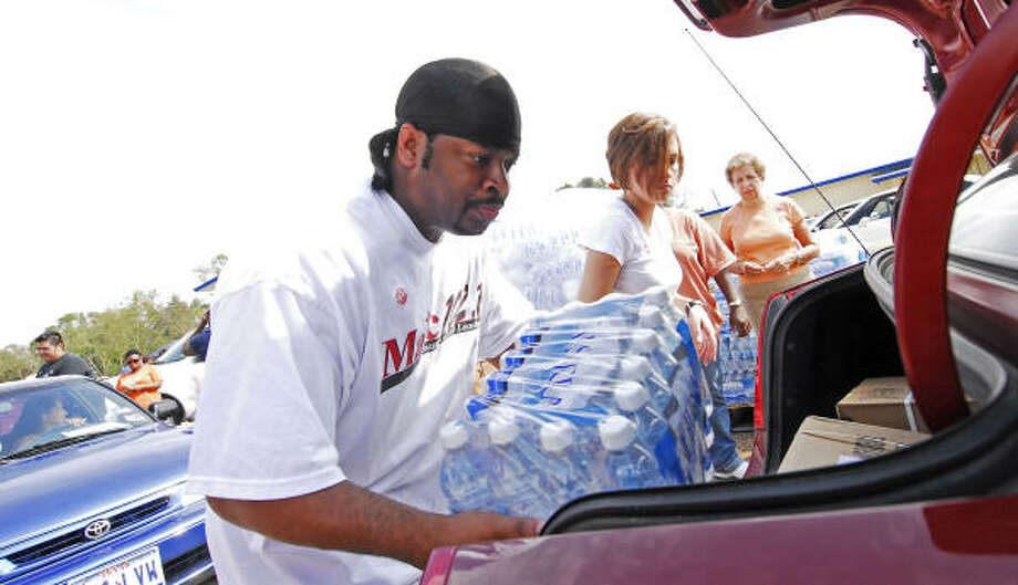 Majic 102 producer Dorail Crayton loads cases of bottled water into cars as people drive through the the Church Without Walls POD site. Photo: Tony Bullard, For The Chronicle
