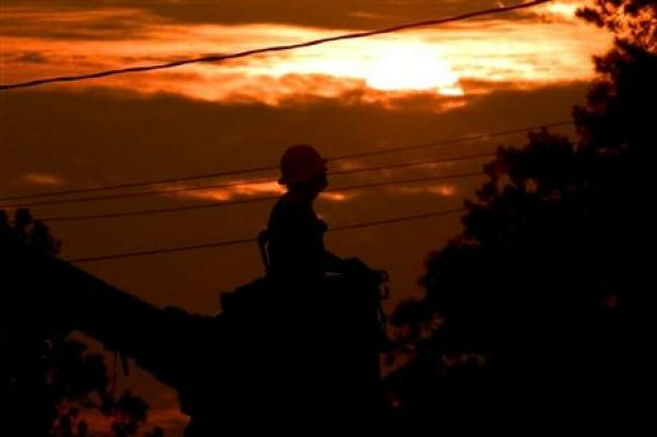 A lineman from Illinois-based GT Electric does an inspection of the power lines as the sun sets. Photo: ThomasM, Chron.Commons Member