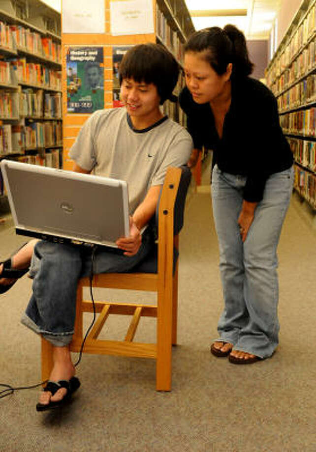 Tuan Cao, 20, left, and his sister, Ann, 24, both of Humble, share some computer time at the Octavia Fields Branch Library in Humble. With their home without power, Tuan was browsing the Internet looking for a used car while Ann, a student at the  University of Houston-Downtown, was working on her online classes. Photo: Jerry Baker, For The Chronicle