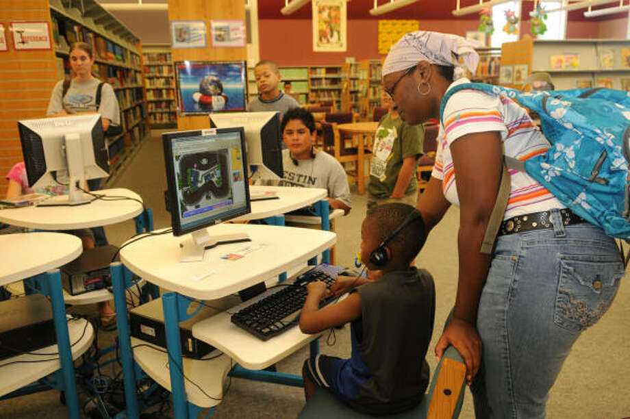 Shemyra Jones, right, of Spring, helps her son, Jaden Tatum, 4, with a computer game during their visit to the Octavia Fields Branch Library in Humble. Jones, who was joined by her daughter, Mikayla Tatum, 9, said that their family has no power at their home. Photo: Jerry Baker, For The Chronicle