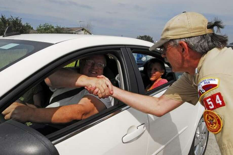 Peter Nahodly, left, thanks Bill Hunn, assistant district commissioner for the Flaming Arrow District of the Sam Houston Area Council of the Boy Scouts of America, after loading up on supplies at the Humble Civic Center. In the back seat is Daniel Miller, 14. Photo: Tony Bullard, For The Chronicle