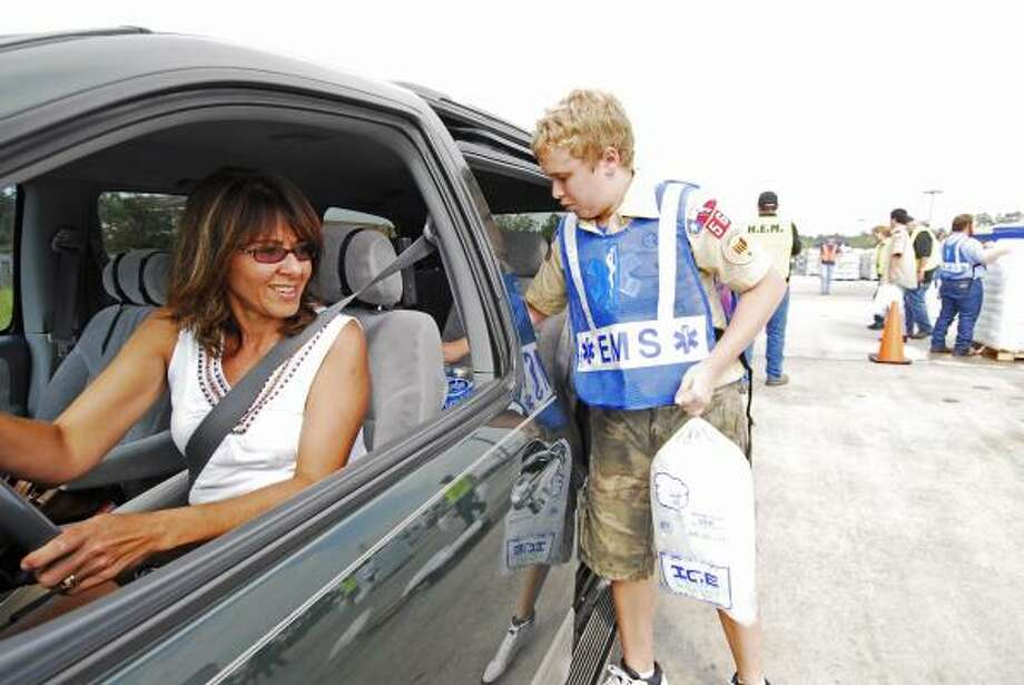 Astrid Chemaly watches as Samuel Chamberlin, 14, of Boy Scout Troop 56, loads bags of ice into her minivan at the Humble Civic Center. Photo: Tony Bullard, For The Chronicle