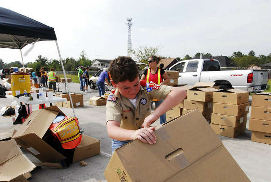 Jake Collier, 12, breaks down cardboard boxes after their contents of box lunches were distributed at the Humble Civic Center. Photo: Tony Bullard, For The Chronicle