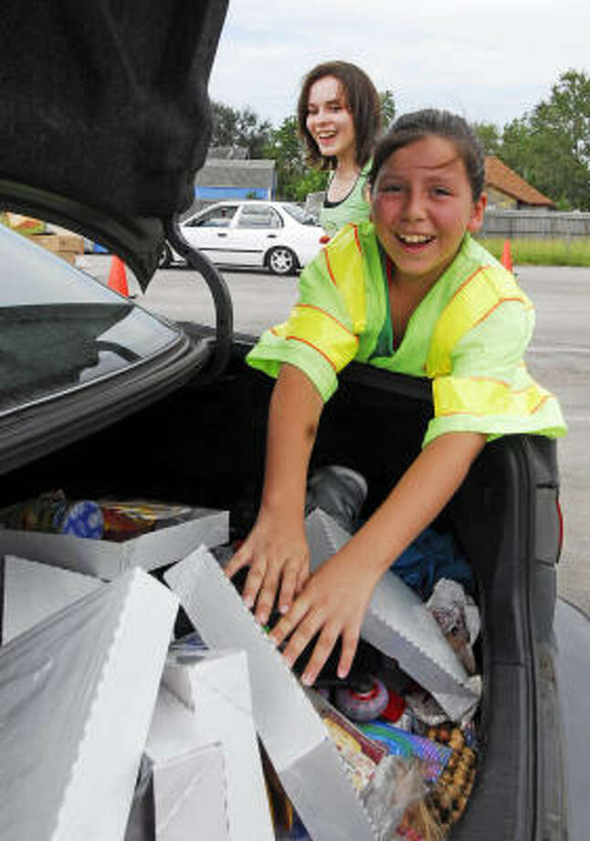 Sisters Michelle, 11, front, and Melissa McDaniel, 16, help load supplies into vehicles at the Humble Civic Center. Photo: Tony Bullard, For The Chronicle