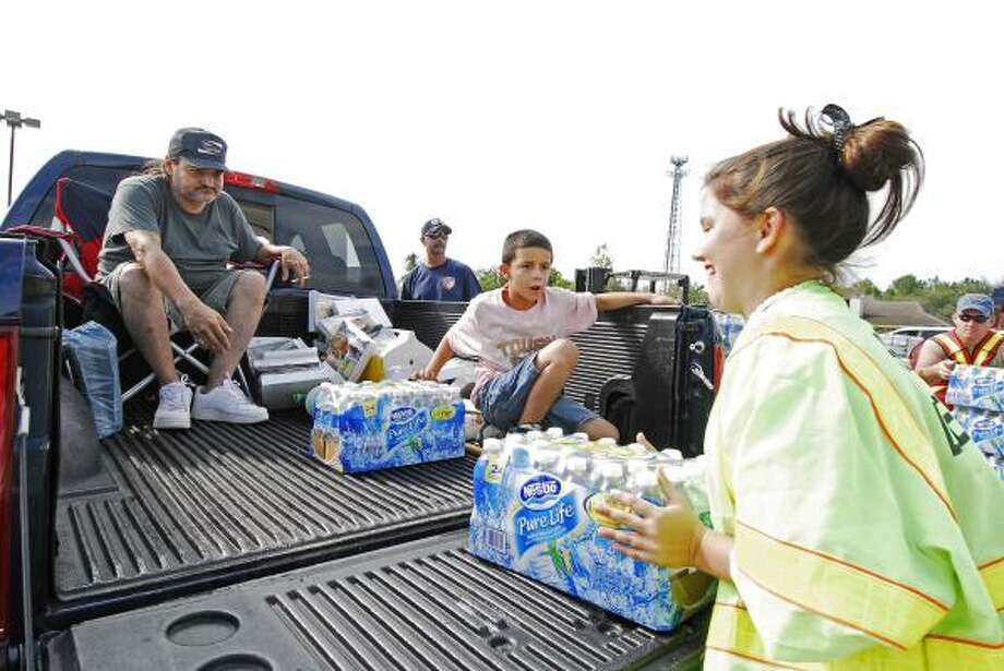Carlos Medrano and Andrew Avila, 8, reach to help Ashley McCurtain, 14, as she loads a couple of cases of water into their truck at the Humble Civic Center. Photo: Tony Bullard, For The Chronicle