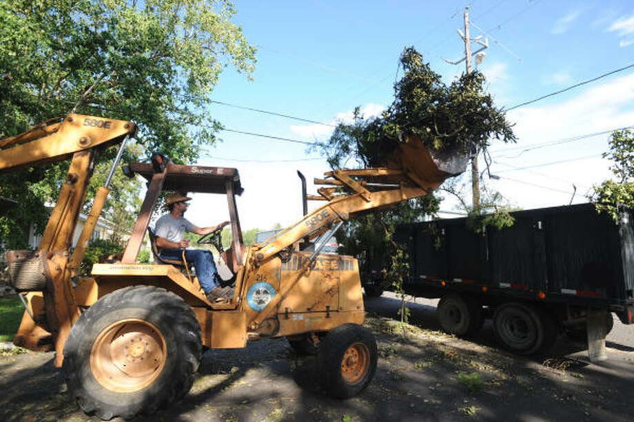 City of Humble worker Clint Coombs clears tree branches along South Avenue A (near Staitti St.) four days after Hurricane Ike passed through Humble/Kingwood area. Photo: Thomas Nguyen, For The Chronicle
