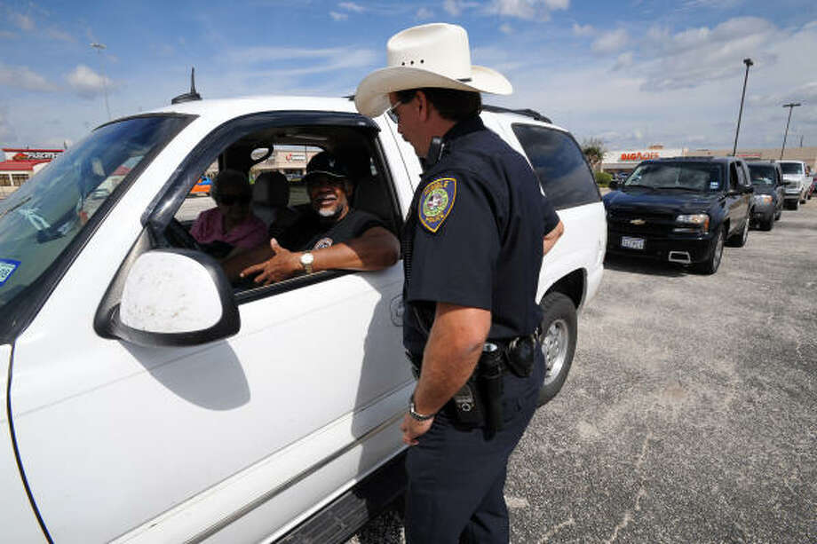 Humble police officer Tony Taylor visits with Ron Williams and Pat Auzenne of Huffman, Texas as they wait to get gas at a Chevron station at the corner of Eastex Freeway Business FM 1960. Photo: Thomas Nguyen, For The Chronicle