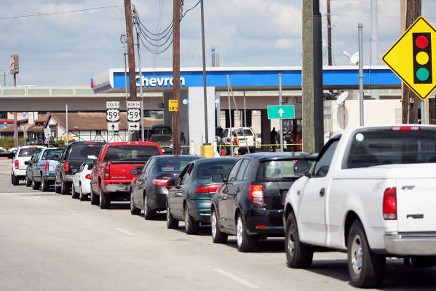 People wait in a long line to get gas at a Chevron station at the corner of Eastex Freeway Business