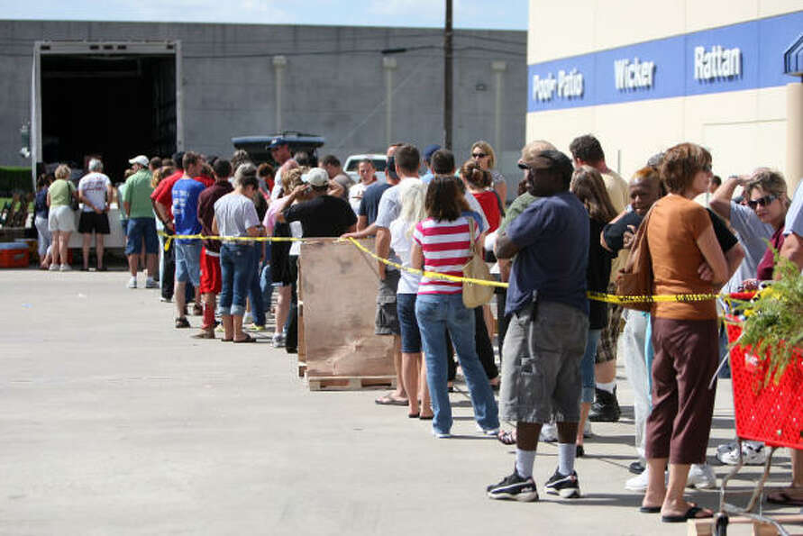 People stand in line to purchase power generators from Silver Dollar Sales in Belmont, Mississippi a