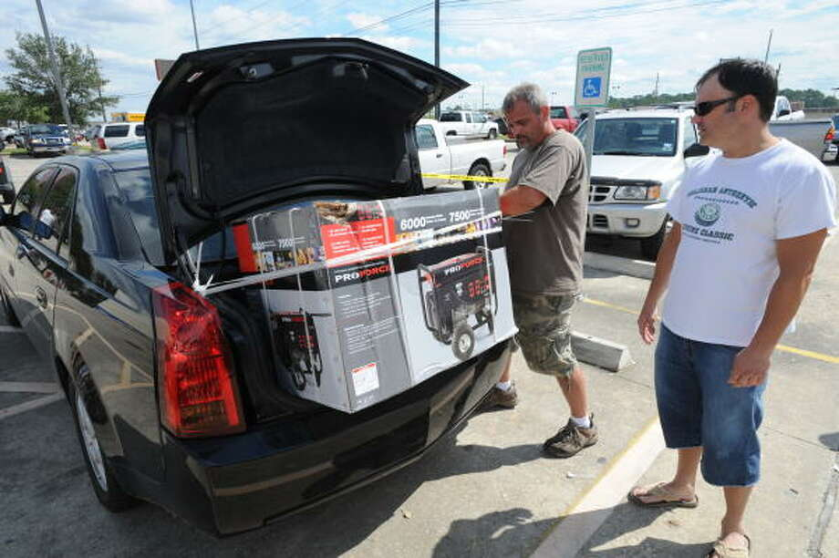 Bryan Miller of The Woodlands, right, purchases a power generator from Silver Dollar Sales in Belmont, Mississippi at a Chair King parking lot at Eastex Freeway, near FM 1960. He's being assisted by Alvin Brown. Photo: Thomas Nguyen, For The Chronicle