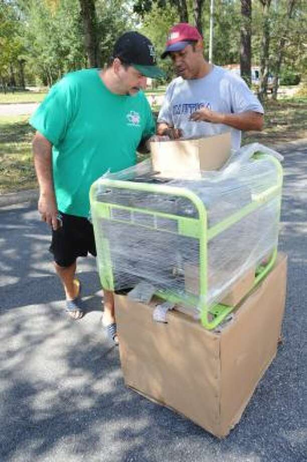 Kingwood resident Joe Russo, left, looks to purchase a power generator from Hector Rojas of Mississippi at the Stein Mart parking lot on the corner of Kingwood Drive and Chestnut Ridge Road. Photo: Thomas Nguyen, For The Chronicle