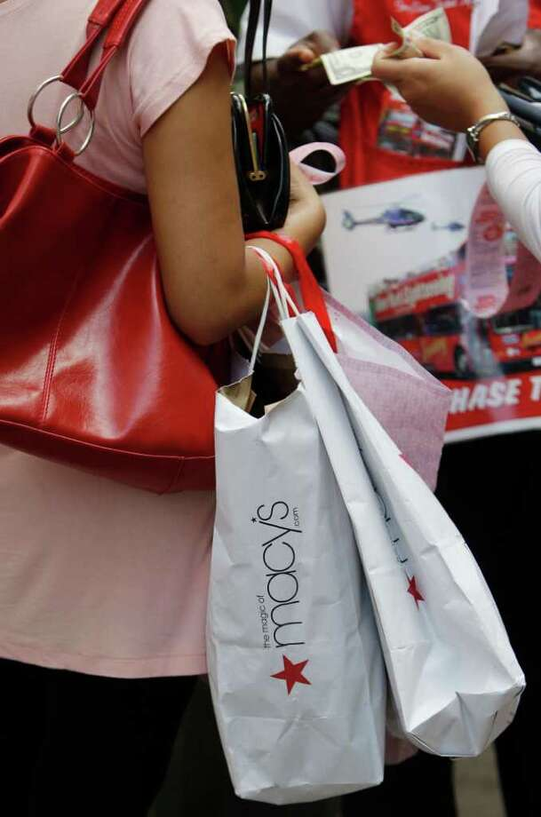 FILE - In this Aug. 4, 2011 file photo, a woman clutches her Macy's shopping bags, in New York. Macy?s Inc. is reporting a 63 percent increase in net income for the second quarter Wednesday, Aug. 10, 2011, as it continues to benefit from its plans to tailor merchandise to local markets. The department store chain is also boosting its full-year profit outlook. (AP Photo/Frank Franklin II, File) Photo: Frank Franklin II, STF / AP