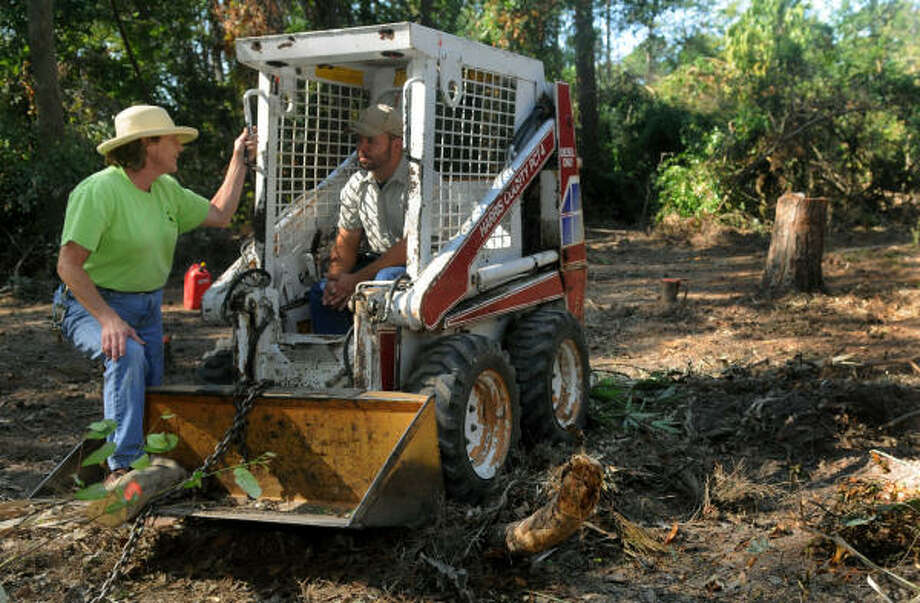 Linda Gay, left, talks to Mercer horticulturist Chris Ludwig, of Cypress, sitting in his skid steer, about how to clear the garden's forest floor that was severely damaged by Hurricane Ike. Photo: Jerry Baker, For The Chronicle