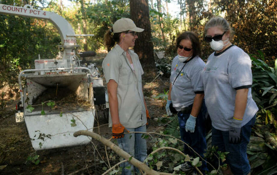 Delores Stevens, left, a member of the horticulture staff at Mercer Arboretum and Botanic Gardens, of Spring, works with volunteers Hermelina Talamantez, center, and her Spring neighbor Wendy Sims, both from Beneficial Finance, to clear tree limbs and brush on the garden's forest floor that was severely damaged by Hurricane Ike. Photo: Jerry Baker, For The Chronicle